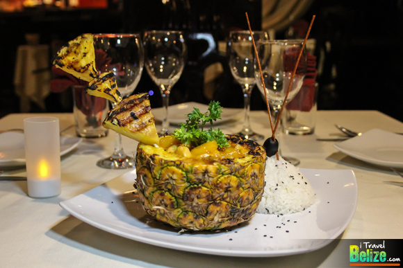 Pineapple Chicken - Fresh pineapple chunks with tender cuts of chicken breast sautéed in ginger, peanut butter sauce with crushed peppers and served in a pineapple