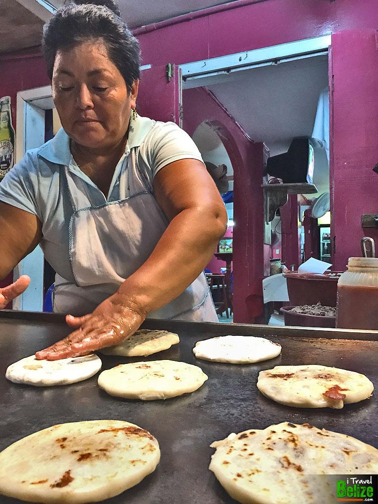 Rice flour pupusas being prepared on the hot comal at Pupuseria Salvadoreno