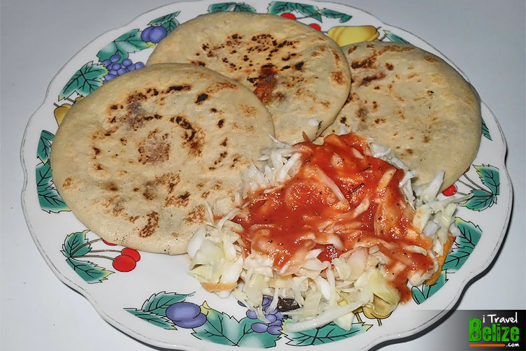 Pupusas are served with a vinegar-based (cabbage & carrot) slaw and tomato sauce